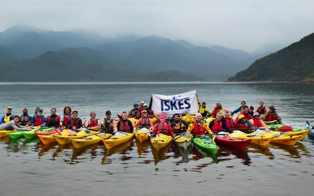 A bunch of people lined up in sea kayaks on the water holding up the ISKES banner