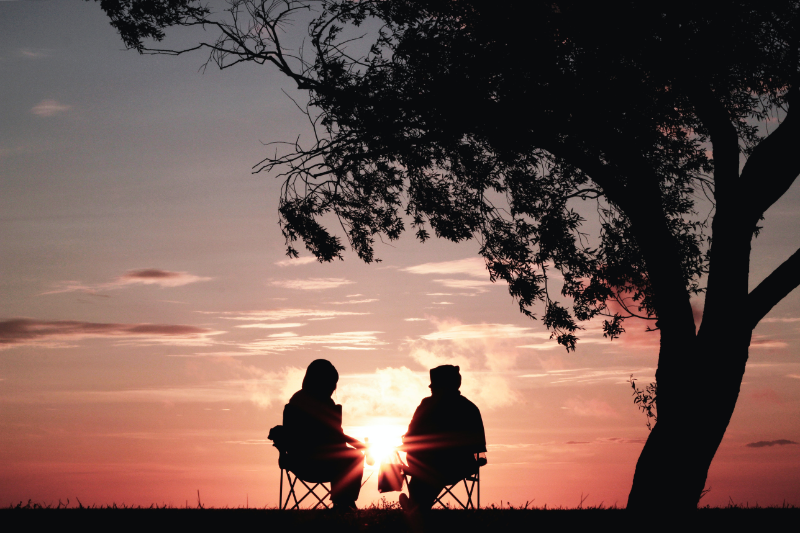 2 people sitting together against a sunset/sunrise silhouette